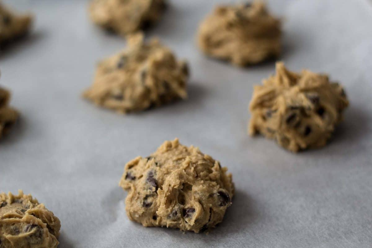 Cookiedej i kugler på bagepapir til chokoladecookies