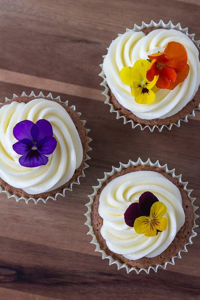 Gulerodsmuffins med ostecreme og pyntet med blomster set oppefra