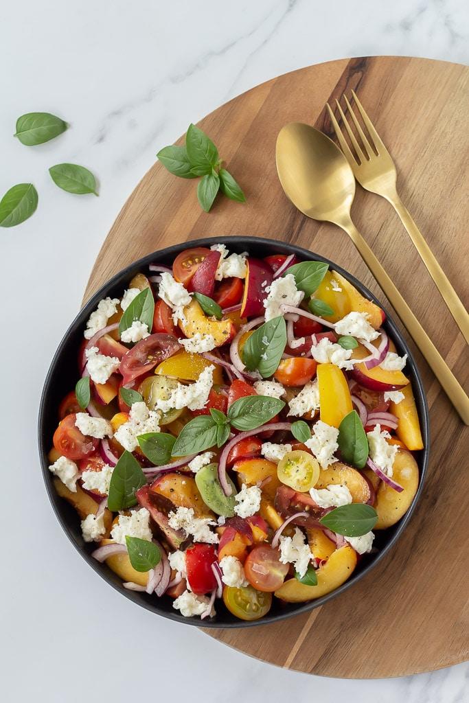 Et sort fad med tomatsalat med nektariner med mange farver. En rigtig sommersalat. Ved siden af ligger guldfarvet salatbestik og lidt basilikum.