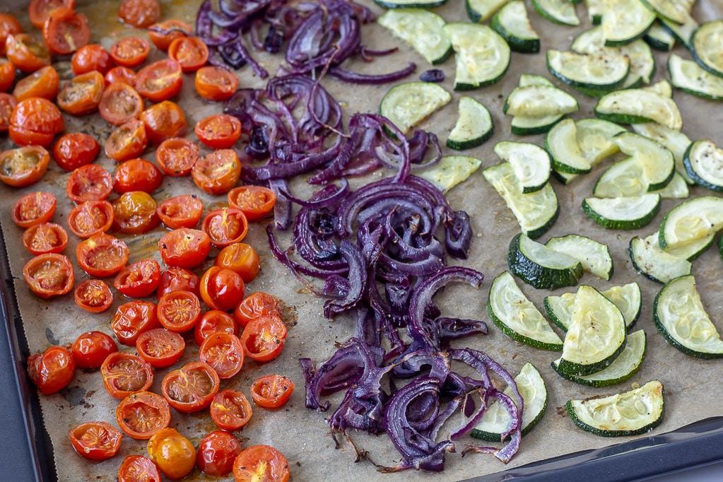 Tomater, rødløg og squash på en bageplade efter ovnen