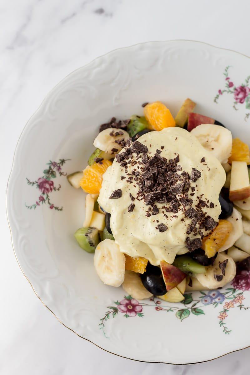 Frugtsalat med råcreme og mørk chokolade i en dyb tallerken